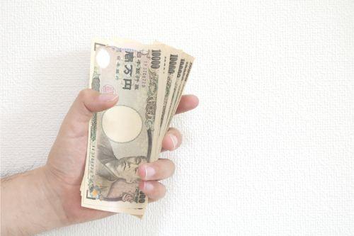 左手で沢山の1万円札を持つ